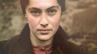 אישה יהודייה עונדת טלאי צהוב מנייר - התמונה שפותחת את התערוכה. צולמה על ידי צלם גרמני