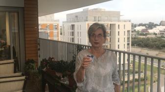 """בילי לניאדו, יושבת ראש עמותת """"דורות ההמשך"""", מדליקה נר נשמה במרפסת. צילום: יח""""צ"""
